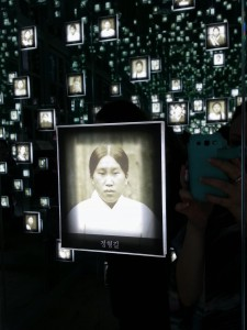 Inside the exhibition hall of women independence activists, a small darkened room with mirrored walls. Glowing from walls are prison photos of the female activists.