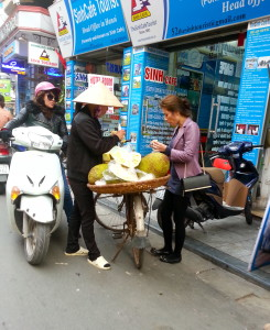 Jack fruit being inspected by a prospective buyer. A lady on her motorbike stops to inspect the sale.