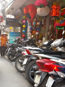 Another colourful sidewalk scene, where motorbikes and lanterns compete for space.