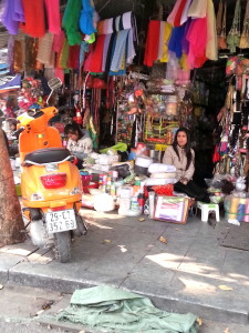 A shop owner chills out in the shade awaiting tourists to buy her wares.