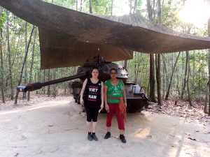 "Bal and I stand next to an abandoned tank. Painted on the side it reads, ""American M41 tank destroyed by a delay mine in 1970."""